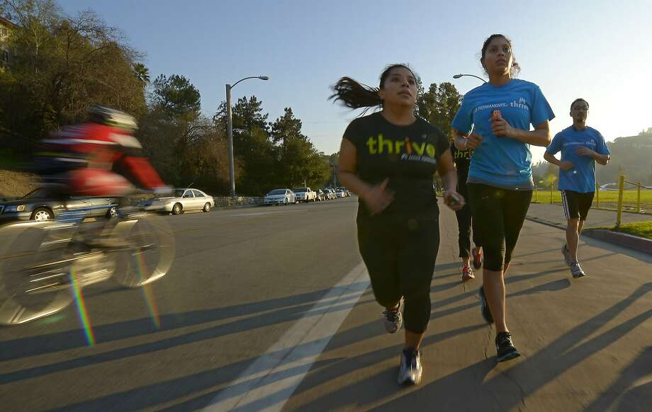 In this Tuesday, Dec. 11, 2012 photo, Zendi Solano, center, trains with running club members Rian Barrett, second from right, and Richard Chen in Pasadena, Calif. Dr. Robert Sallis says some patients may not be aware that research shows physical inactivity is riskier than high blood pressure, obesity and other health risks people know they should avoid. As recently as November 2012, a government-led study concluded that people who routinely exercise live longer than others, even if they're overweight. (AP Photo/Mark J. Terrill) Photo: Mark J. Terrill, Associated Press