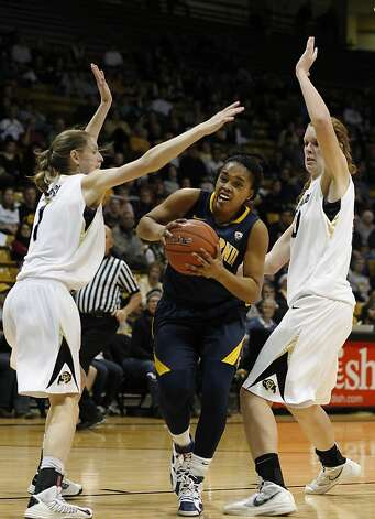 Brittany Boyd, who had a team-high 15 points and six assists, slips between Colorado's Lexy Kresl (left) and Rachel Hargis. Photo: David Zalubowski, Associated Press