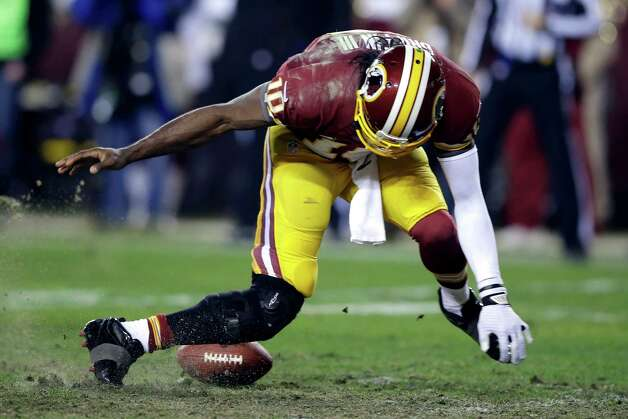 Washington Redskins quarterback Robert Griffin III twists his knees as he reaches for the loose ball after a low snap during the second half of an NFL wild card playoff football game against the Seattle Seahawks in Landover, Md., Sunday, Jan. 6, 2013. (AP Photo/Matt Slocum) Photo: Matt Slocum, Associated Press / AP