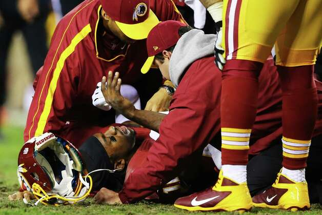 LANDOVER, MD - JANUARY 06:  Robert Griffin III #10 of the Washington Redskins receives attention after he was injured on a bad snap in the fourth quarter against the Seattle Seahawks during the NFC Wild Card Playoff Game at FedExField on January 6, 2013 in Landover, Maryland. Photo: Al Bello, Getty Images / 2013 Getty Images