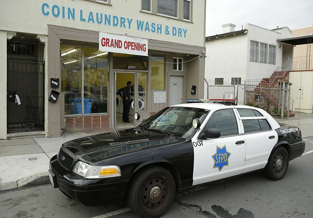 """A San Francisco police car is parked in front of a laundromat where an argument started, which resulted in a woman being set on fire Sunday, Jan. 6, 2013, in San Francisco. San Francisco police say a woman is hospitalized with what are being described as """"life-threatening injuries"""" after someone poured a flammable liquid on her and set her on fire. (AP Photo/Ben Margot)"""