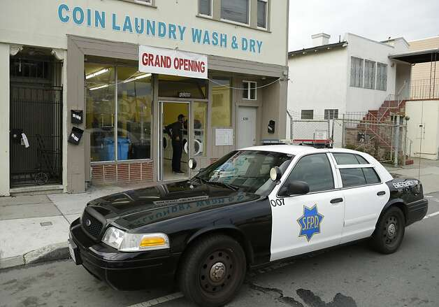 "A San Francisco police car is parked in front of a laundromat where an argument started, which resulted in a woman being set on fire Sunday, Jan. 6, 2013, in San Francisco. San Francisco police say a woman is hospitalized with what are being described as ""life-threatening injuries"" after someone poured a flammable liquid on her and set her on fire.  (AP Photo/Ben Margot) Photo: Ben Margot, Associated Press"