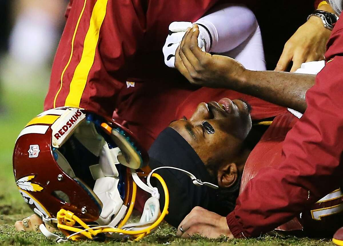 LANDOVER, MD - JANUARY 06: Robert Griffin III #10 of the Washington Redskins is injured on a bad snap in the fourth quarter against the Seattle Seahawks during the NFC Wild Card Playoff Game at FedExField on January 6, 2013 in Landover, Maryland. (Photo by Al Bello/Getty Images)