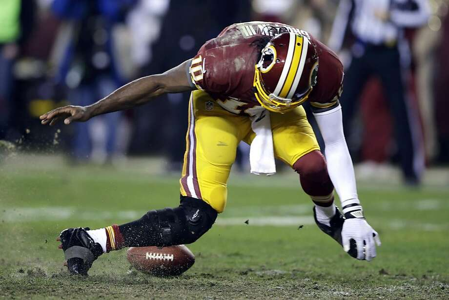 Washington Redskins quarterback Robert Griffin III twists his knees as he reaches for the loose ball after a low snap during the second half of an NFL wild card playoff football game against the Seattle Seahawks in Landover, Md., Sunday, Jan. 6, 2013. (AP Photo/Matt Slocum) Photo: Matt Slocum, Associated Press