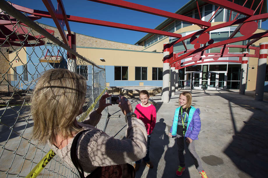 Holly Pearson takes a photo of 8-year-old twins Anna (center) and Ashleigh during the open house at Vineyard Ranch Elementary School at 16818 Huebner Road. The open house was so well-attended, officials ran out of the maps they'd printed. Photo: Michael Miller, San Antonio Express-News / San Antonio Express-News