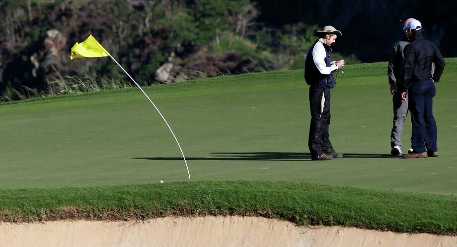 The flexibility of the flag on the 12th hole is put to the test on Sunday. Photo: Elaine Thompson, STF / AP