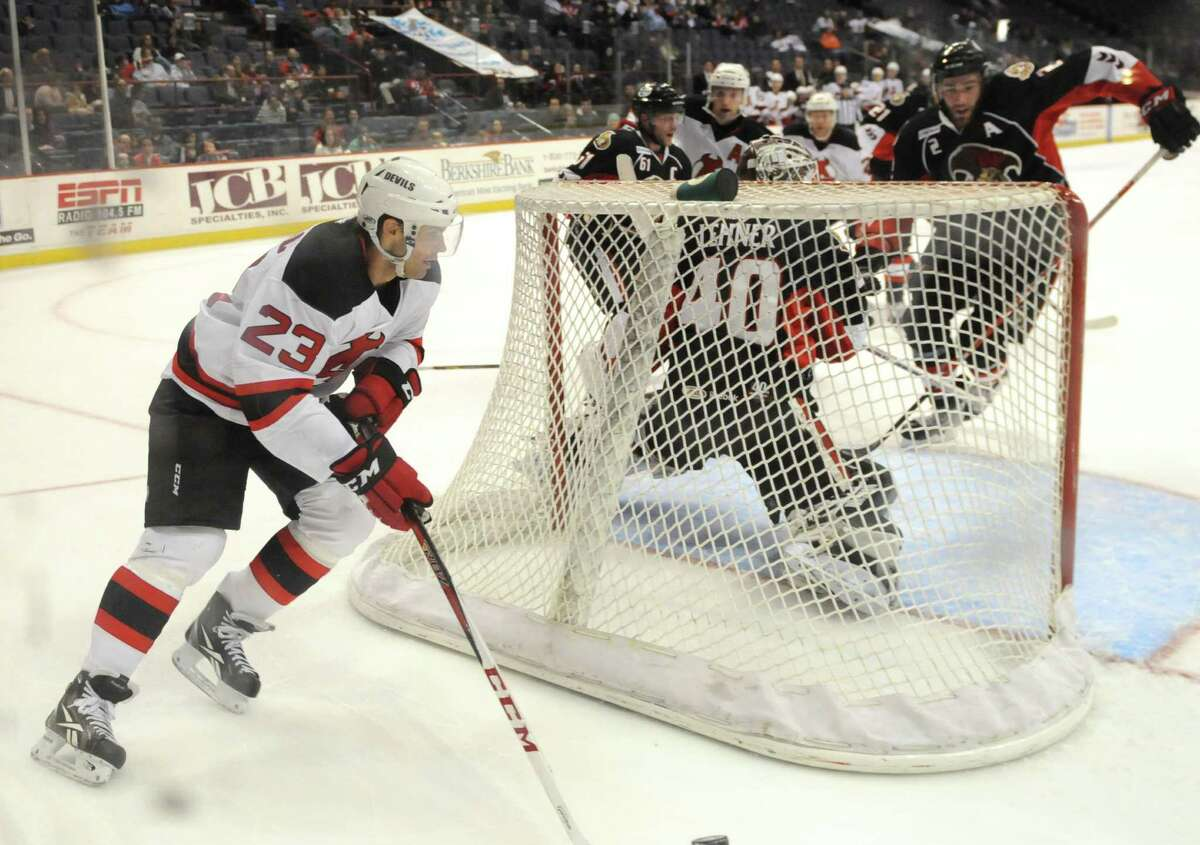 Darcy Zajac of the Albany Devils, left, works behind the Binghamton Senators goal, Sunday evening, Jan. 6, 2013, during the second period at the Times Union Center in Albany, N.Y.