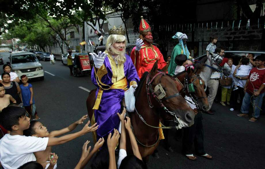 Filipino kids scramble to get candies given by men dressed as the Three Kings during Epiphany celebrations in Manila, Philippines on Sunday Jan. 6, 2013. Christmas in this dominantly Roman Catholic nation officially ends on the Feast of the Three Kings, also known as the Feast of the Epiphany. (AP Photo/Aaron Favila) Photo: AARON FAVILA