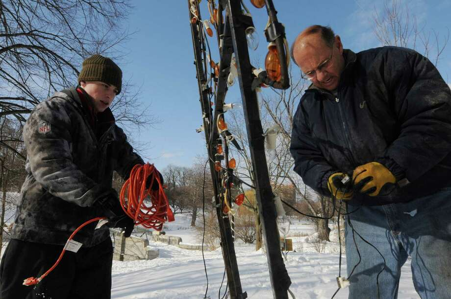 Nick Brockley of Voorheesville, left, and Tom Mahoney of Colonie, treasurer for the Albany Police Athletic League, dismantle a section of the Annual Capital Holiday Lights Sunday morning, Jan. 6, 2013, in Albany's Washington Park. Volunteers are needed daily and may report to the Lake House starting at 8:30 a.m. The annual show benefits  the Albany Police Athletic League (PAL), which helps at-risk youth in the Capital Region. (Will Waldron/Times Union) Photo: Will Waldron