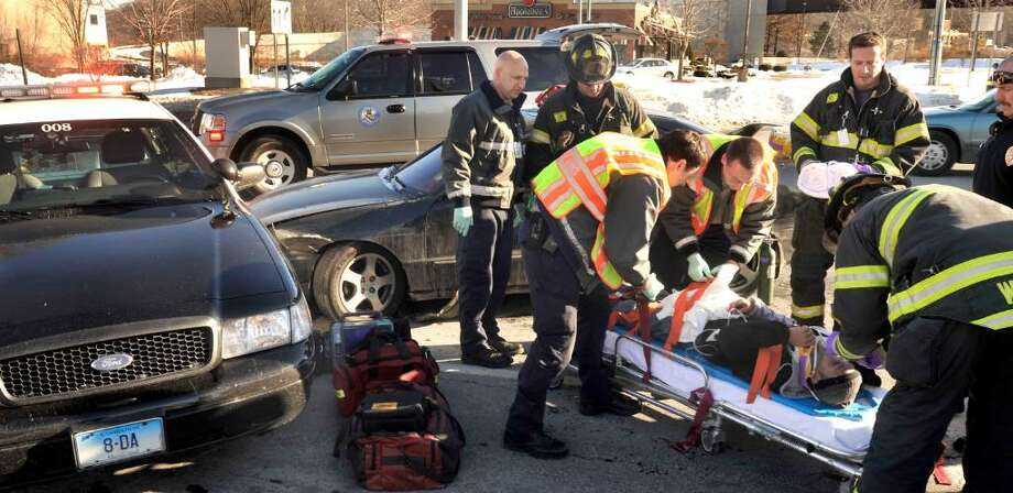 The driver of a car that hit a police crusier is taken to the ambulance by first responders, in Danbury, at 9:45 A.M., on Tuesday, Dec.22, 2009. Photo: Michael Duffy / The News-Times