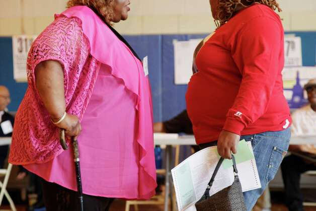 In this June 26, 2012, photo, two overweight women hold a conversation in New York. A new poll suggests that while more than 7 in 10 Americans can correctly tick off heart disease and diabetes as obesity's most serious consequences, few Americans are aware of the lesser-known health consequences_ such as worsening some types of cancer, arthritis, sleep apnea and even infertility.  Only about one-quarter of people think it's possible for someone to be very overweight and still healthy, according to the poll by The Associated Press-NORC Center for Public Affairs Research. (AP Photo/Mark Lennihan) Photo: Mark Lennihan