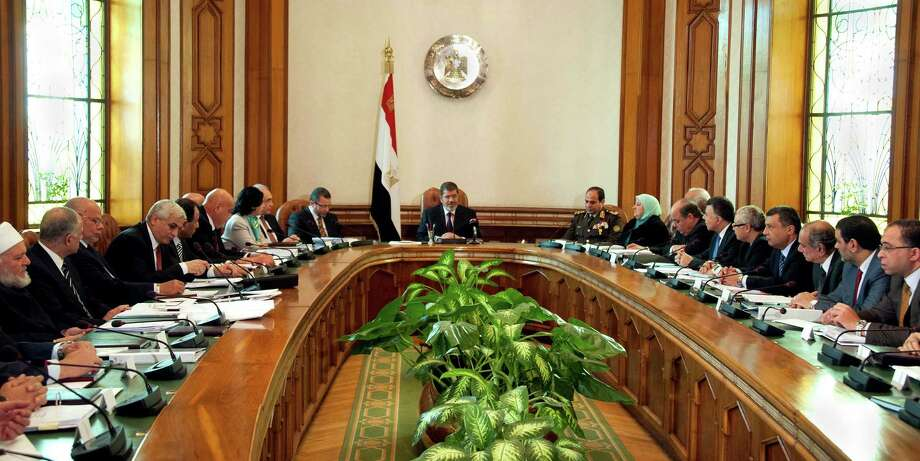 In this image released by the Egyptian Presidency, President Mohammed Morsi, center, meets with his cabinet including 10 new ministers after their swearing in at the presidential palace in Cairo, Egypt, Sunday Jan. 6, 2013. Egypt?s government swore in 10 new ministers on Sunday in a Cabinet shake-up aimed at improving the government?s handling of the country?s struggling economy as foreign reserves levels slid closer to $15 billion, just enough to cover three months? worth of imports. (AP Photo/Egyptian Presidency) Photo: Anonymous, HOEP / Egyptian Presidency