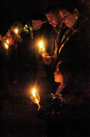 Heather, Breeze and Kris Montalvo of Lumberton hold candles in a ceremonial bonfire Sunday night at St. Mark Episcopal Church. The Burning of the Greens is a yearly tradition dating back many years, enjoyed by church members and guests for its symbolic and corporeal delights. Photo: Sarah Moore