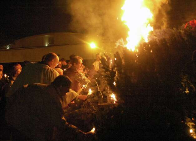 Church members and guests use candles to light a bonfire of Christmas evergreens after the Epiphany service Sunday at St. Mark's Episcopal Church. The bonfire, known as the Burning of the Greens, is a favorite yearly tradition of long standing. Photo: Sarah Moore