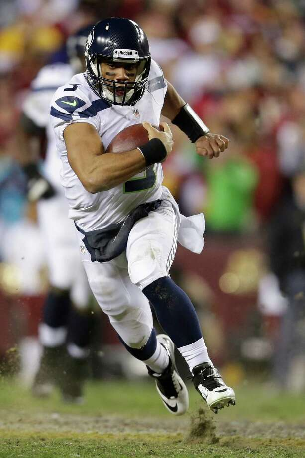 Seattle Seahawks quarterback Russell Wilson scrambles with the ball during the second half of an NFL wild card playoff football game against the Washington Redskins in Landover, Md., Sunday, Jan. 6, 2013. Photo: AP