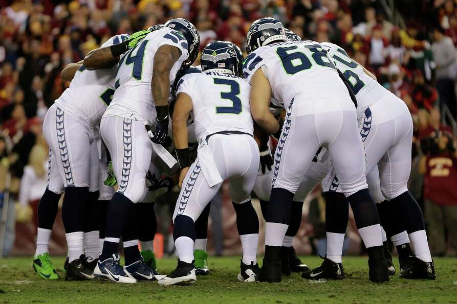 Seattle Seahawks quarterback Russell Wilson leads the team huddle during the first half of an NFL wi