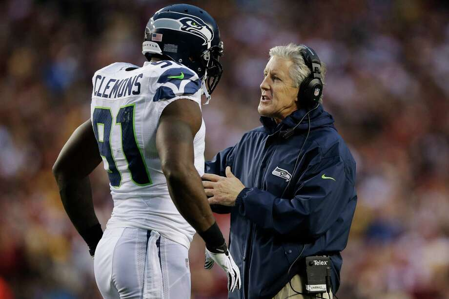 Seattle Seahawks head coach Pete Carroll talks with Seattle Seahawks defense end Chris Clemmons. Photo: AP