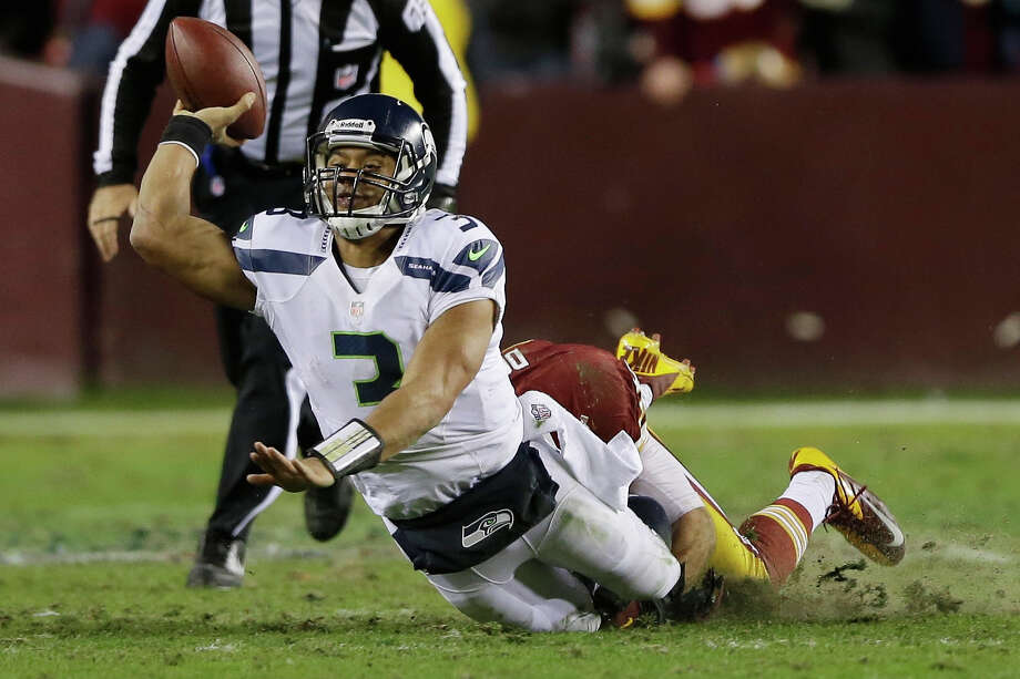 Seattle Seahawks quarterback Russell Wilson passes the ball as he's dragged down by Washington Redskins strong safety Reed Doughty during the second half of an NFL wild card playoff football game in Landover, Md., Sunday, Jan. 6, 2013. Photo: AP
