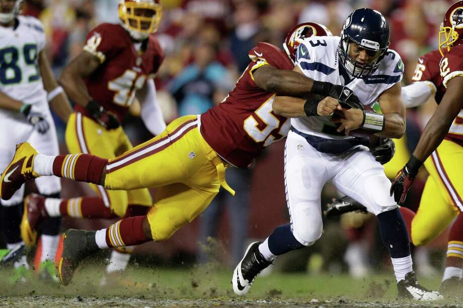 Seattle Seahawks quarterback Russell Wilson is stopped by Washington Redskins inside linebacker London Fletcher during the first half of an NFL wild card playoff football game in Landover, Md., Sunday, Jan. 6, 2013. Photo: AP