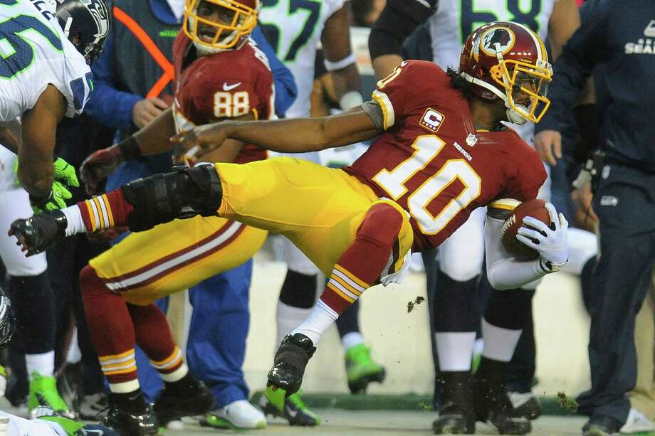 Washington Redskins quarterback Robert Griffin III flies through the air as he is knocked out of bounds during the first half of an NFL wild card playoff football game against the Seattle Seahawks in Landover, Md., Sunday, Jan. 6, 2013. Photo: AP