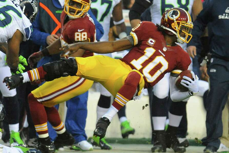 Washington Redskins quarterback Robert Griffin III flies through the air as he is knocked out of bou