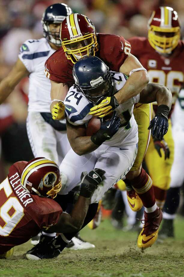 CORRECTS TO REMOVE REFERENCE TO TOUCHDOWN - Seattle Seahawks running back Marshawn Lynch drags Washington Redskins inside linebacker London Fletcher and outside linebacker Ryan Kerrigan on a run during the second half of an NFL wild card playoff football game in Landover, Md., Sunday, Jan. 6, 2013. Photo: AP