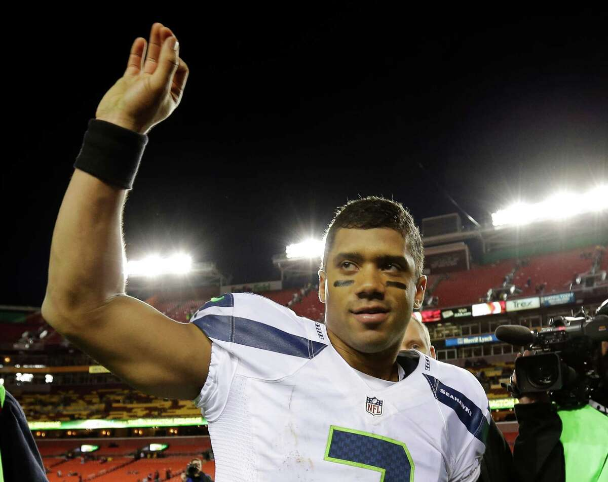 Seattle Seahawks quarterback Russell Wilson waves as he leaves the field after an NFL wild card playoff football game against the Washington Redskins in Landover, Md., Sunday, Jan. 6, 2013. The Seahawks defeated the Redskins 24-14.