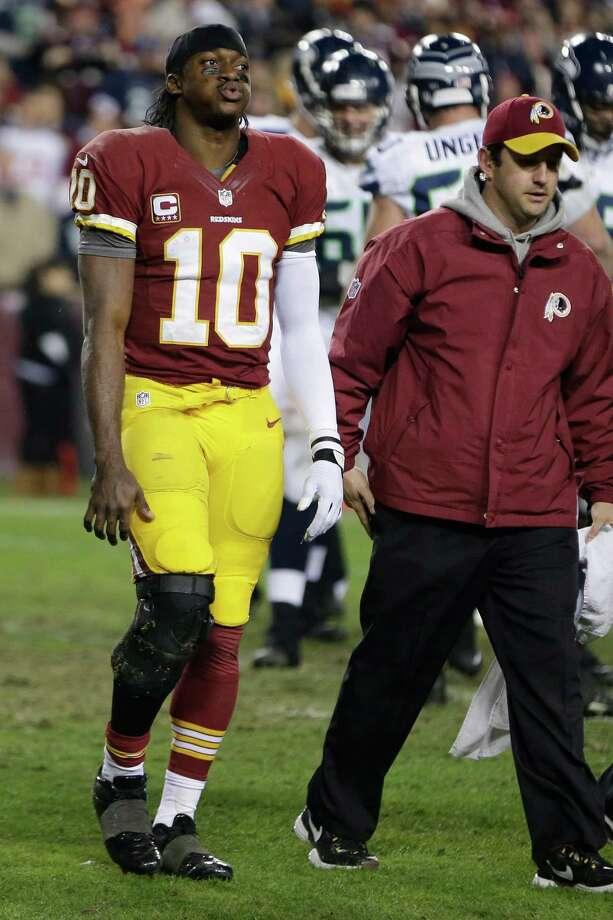 Washington Redskins quarterback Robert Griffin III walks off the field after twisting his knee during the second half of an NFL wild card playoff football game against the Seattle Seahawks in Landover, Md., Sunday, Jan. 6, 2013. Photo: AP