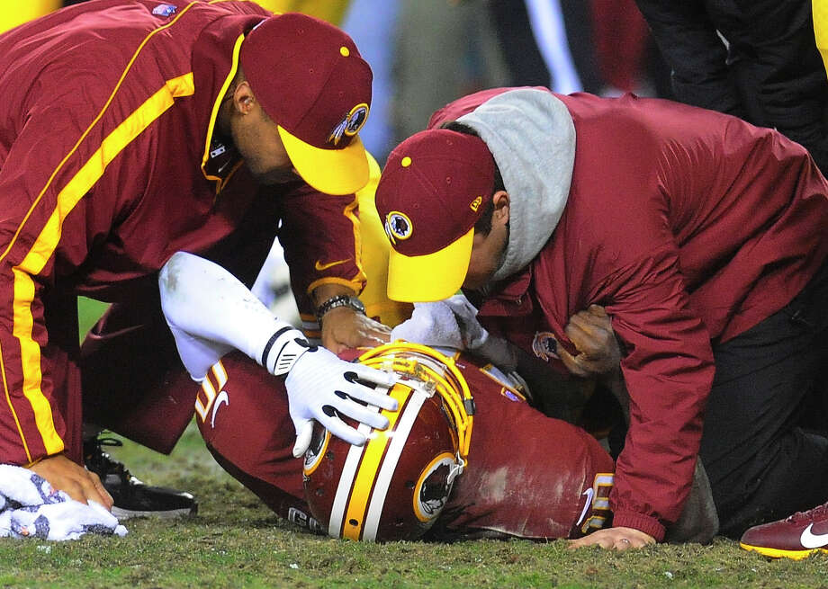 Trainers tend to injured Washington Redskins quarterback Robert Griffin III during the second half of an NFL wild card playoff football game against the Seattle Seahawks in Landover, Md., Sunday, Jan. 6, 2013. Photo: AP
