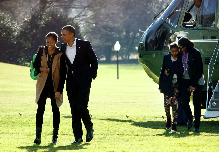 President Barack Obama,  with daughter Malia and first lady Michelle Obama and daughter Sasha, arrives at the White House Sunday after a winter vacation  in Hawaii. Photo: Pool / 2012 Getty Images