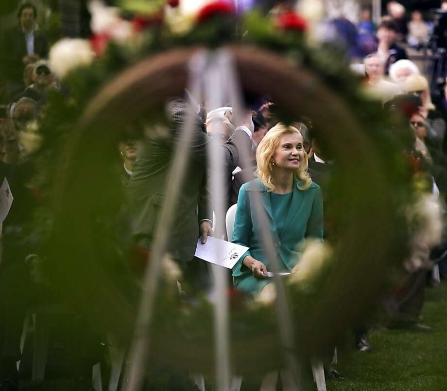 Tricia Nixon Cox, daughter of the 37th United States President Richard M. Nixon, is framed in a wreath honoring her father during a commemoration of the 100th anniversary of the birth of Richard Nixon at the Richard Nixon Presidential Library in Yorba Linda, Calif., Sunday, Jan. 6, 2013. Photo: Chris Carlson, Associated Press