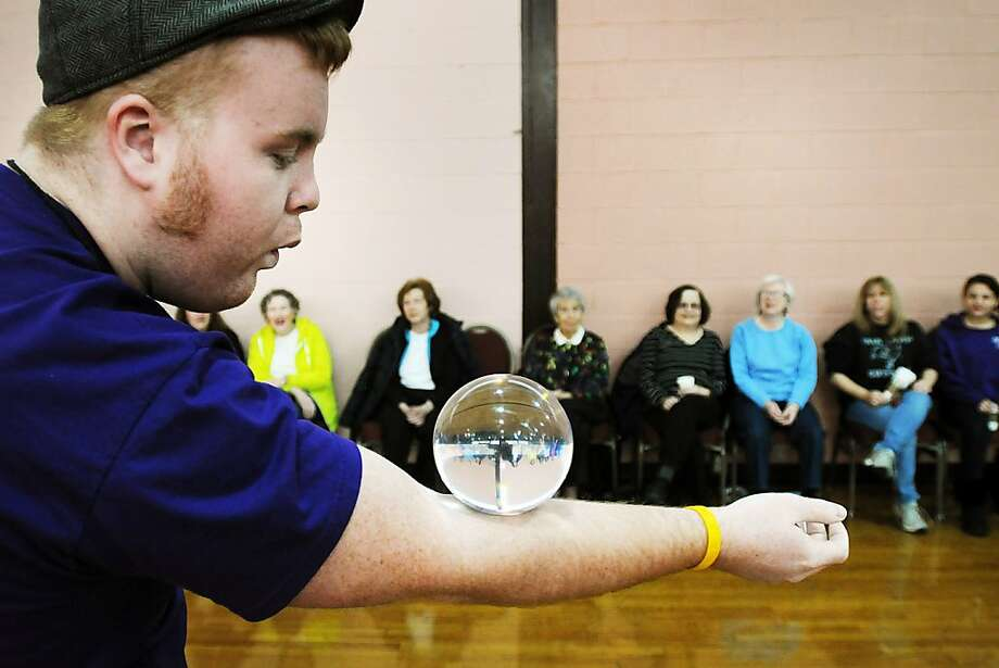 Danny Mulqueen, from Circus Place, demonstrates a contact juggling ball as participants watch during a Circus Skills Workshop experience, Sunday, Jan. 6, 2013, at Jewish Community Center in Paramus, N.J. Photo: Mitsu Yasukawa, Associated Press