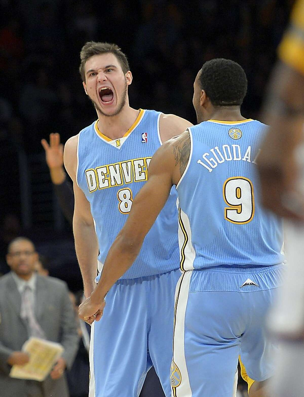 Denver Nuggets forward Danilo Gallinari, left, of Italy, celebrates with teammate Andre Iguodala after hitting a three point shot late in the second half of their NBA basketball game against the Los Angeles Lakers, Sunday, Jan. 6, 2013, in Los Angeles. The Nuggets won 112-105. (AP Photo/Mark J. Terrill)