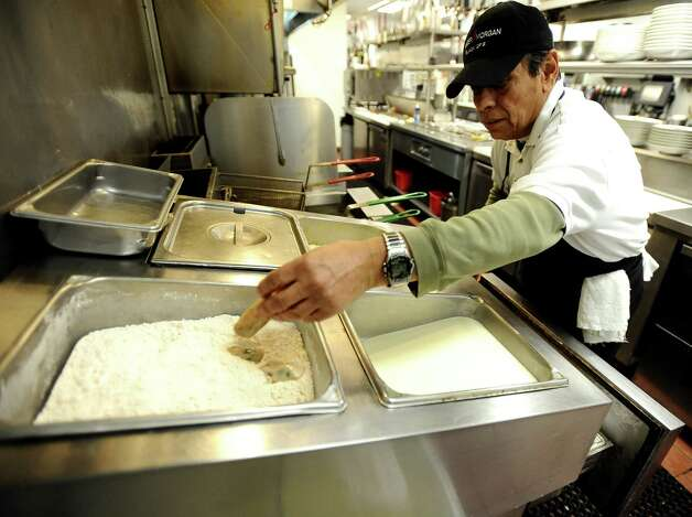 Cook Carlos Lee batters the raw oysters for an oyster po boy at Suga's Deep South Cuisine & Jazz Bar in Beaumont on Thursday, January 3, 2013. Photo taken: Randy Edwards/The Enterprise