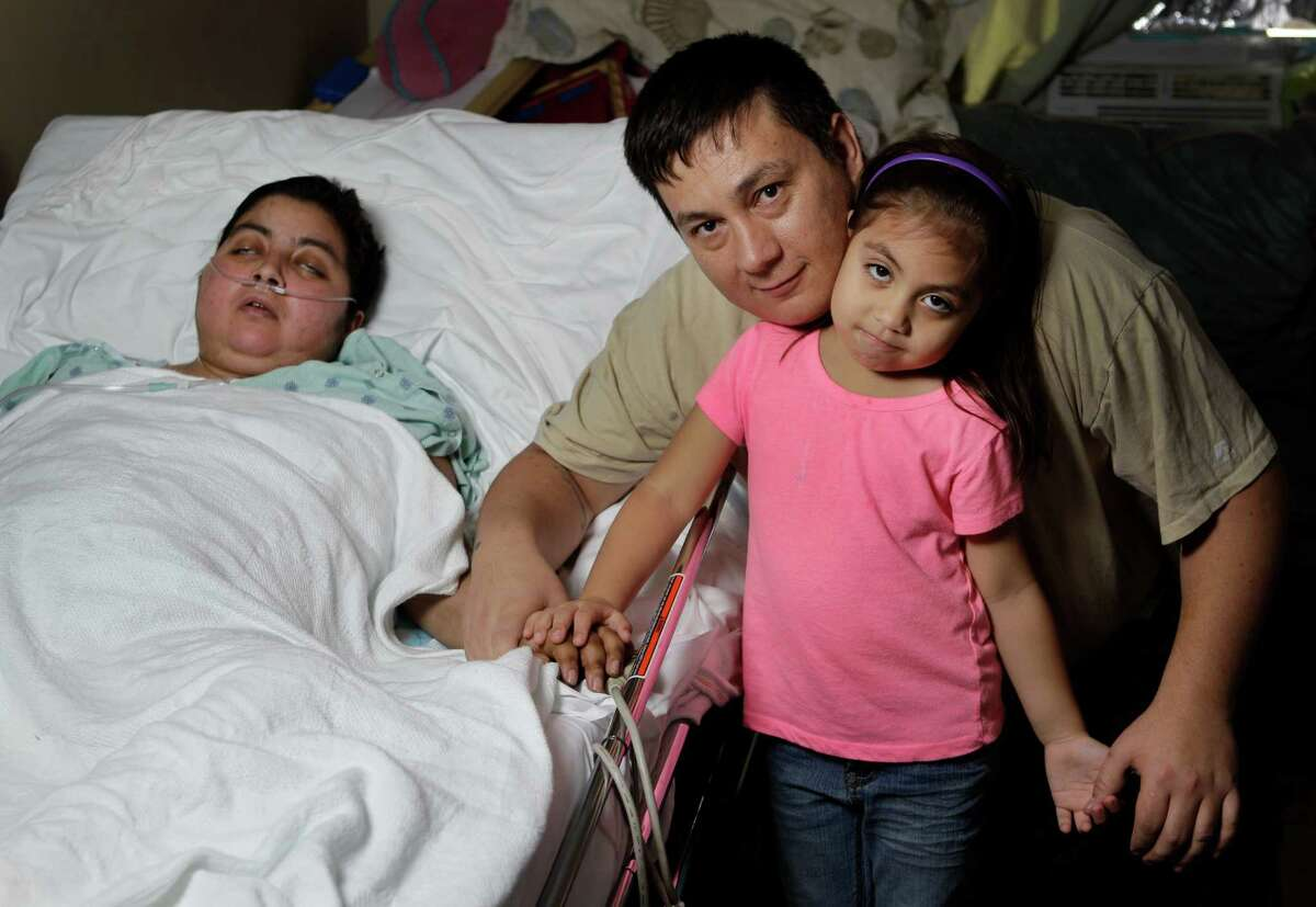 Luis Aguillon and his daughter Melissa Aguillon, 4, sit at Maria Sanchez's bedside last month.