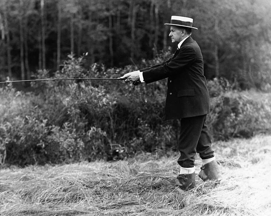 Former President Calvin Coolidge appears in a straw hat and rubber boots in a stream near the Coolidge family homestead in Plymouth, Vt., on July 14, 1931. A number of the speckled denizens left Plymouth streams for the frying pan after Coolidge returned for a brief vacation. Photo: Associated Press / Associated Press