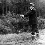 Former President Calvin Coolidge appears in a straw hat and rubber boots in a stream near the Coolidge family homestead in Plymouth, Vt., on July 14, 1931. A number of the speckled denizens left Plymouth streams for the frying pan after Coolidge returned for a brief vacation.