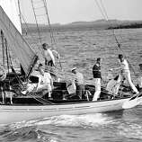 Activity aboard the Amberjack 11, with all hands busy at some appointed task, as the presidential vacation yacht sailed on June 26, 1933 in Penobscot Bay, Maine. The president's son,  James Roosevelt (dark sweater), is assisting his brother, John, to haul in the main sail.    Seated in extreme right in the stern of the craft is Franklin Jr.   At the wheel (with back to camera), between James and John, is President  Franklin Roosevelt.