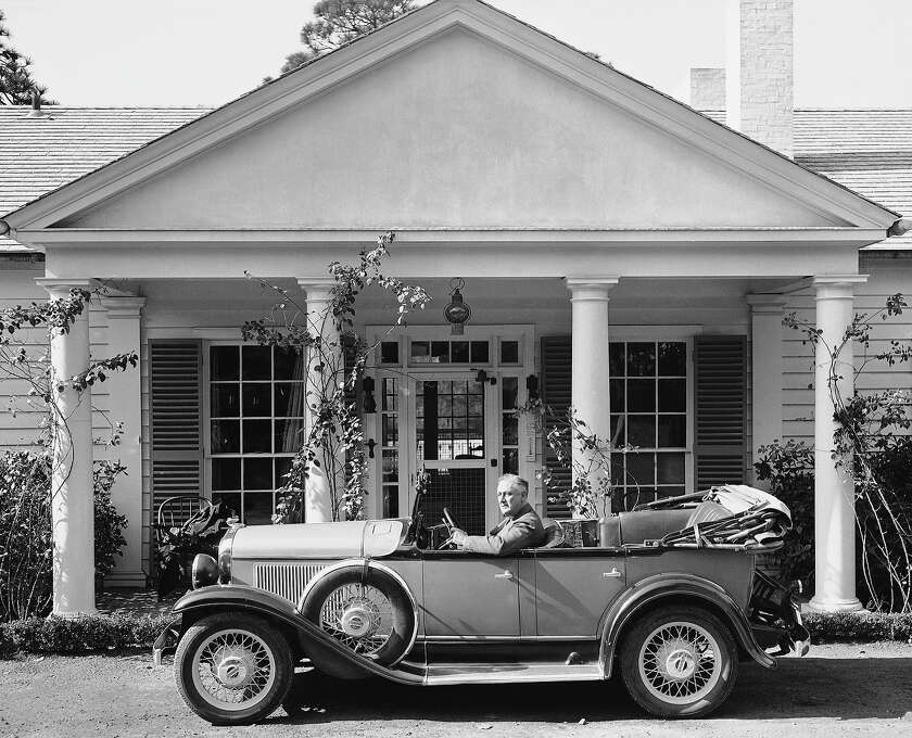 """Georgia sunshine and country roads attracted President Franklin Roosevelt on the first day of his vacation in Nov. 22, 1935 in Warm Springs. Georgia. At the wheel of his automobile, the president waves as he prepares to leave the """"Little White House"""" for a drive into the picturesque countryside.   Motoring and swimming were the chief executive's principal diversions. Photo: Associated Press / Associated Press"""