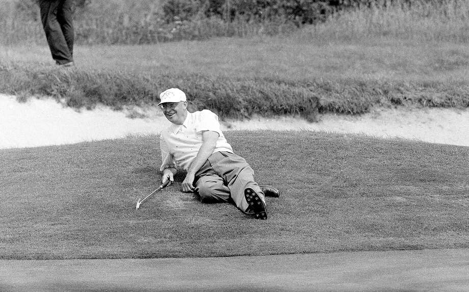 In this Sept. 10, 1957, file photo, President Dwight Eisenhower relaxes at the 18th hole during a golf game in Newport, R.I. Photo: Associated Press / Associated Press
