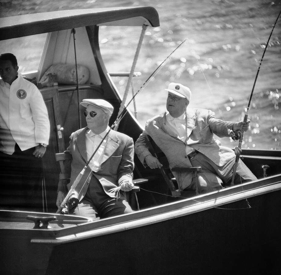 President Dwight Eisenhower and his friend George E. Allen listen for the replay after an aide hollered over to a commercial fisherman on a nearby boat asking for advice on bait at Block Island, R.I., on Sept. 3, 1958. The president, vacationing at nearby Newport, is holding a feather lure that had failed to attract any fish after several hours of trolling. Photo: Associated Press / Associated Press