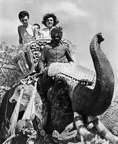 Mrs. Jacqueline Kennedy's hair flew in the wind as she took an elephant ride during her visit to Jaipur, India on March 19, 1962.    Riding in the golden seat beside her was her sister, Princess Lee Radziwill.  The gaily decorated animal, a female named Bibia, was fitted with false tusks carved from wood. Photo: Associated Press / Associated Press