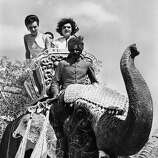 Mrs. Jacqueline Kennedy's hair flew in the wind as she took an elephant ride during her visit to Jaipur, India on March 19, 1962.    Riding in the golden seat beside her was her sister, Princess Lee Radziwill.  The gaily decorated animal, a female named Bibia, was fitted with false tusks carved from wood.