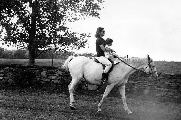 First lady Jacqueline Kennedy holds her son John F. Kennedy Jr. as she rides towards her family's home at Hammersmith Farm, where she spent her vacation, on Sept. 12, 1962, near Newport, R.I. Photo: Associated Press / Associated Press