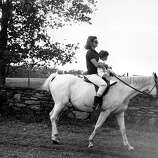 First lady Jacqueline Kennedy holds her son John F. Kennedy Jr. as she rides towards her family's home at Hammersmith Farm, where she spent her vacation, on Sept. 12, 1962, near Newport, R.I.
