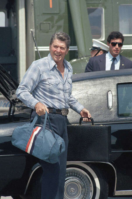 U.S. President Ronald Reagan carries briefcase and duffel bag as he arrives at the airport, Aug., 26, 1984 in Santa Monica, Calif. Reagan, who was on vacation at his ranch in Santa Barbara, arrived in Los Angeles for three days of private meetings. Photo: Associated Press / Associated Press