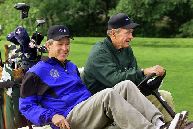 President George W. Bush, celebrating his 55th birthday, smiles as his father, former President Bush, steers their golf cart at the Cape Arundel Golf Club in Kennebunkport, Maine, July 6, 2001. The family group included Bush's parents, former President Bush and former first lady Barbara Bush, sister Dorothy and brother Jeb, the governor of Florida. Photo: Associated Press / Associated Press