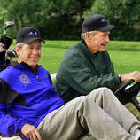 President George W. Bush, celebrating his 55th birthday, smiles as his father, former President Bush, steers their golf cart at the Cape Arundel Golf Club in Kennebunkport, Maine, July 6, 2001. The family group included Bush's parents, former President Bush and former first lady Barbara Bush, sister Dorothy and brother Jeb, the governor of Florida.
