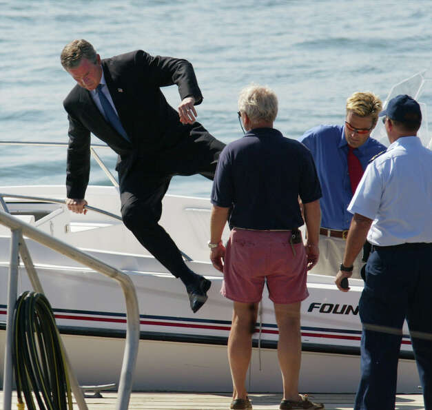President Bush leaps over the side of his father's speedboat, Fidelity II, as they arrive in Scarbor