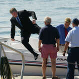 President Bush leaps over the side of his father's speedboat, Fidelity II, as they arrive in Scarborough, Maine, to campaign for Sen. Susan Collins, R-Maine, Aug. 3, 2002.